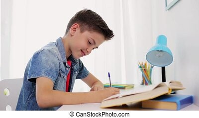 happy boy with book writing to notebook at home