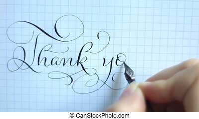 Text thank you with a pen on a sheet of paper. Calligraphy...