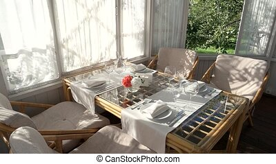 Table with plates and glasses. Summer behind the window....