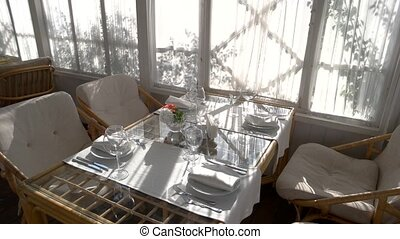Chairs and dining table. Tableware, flowers in vase....