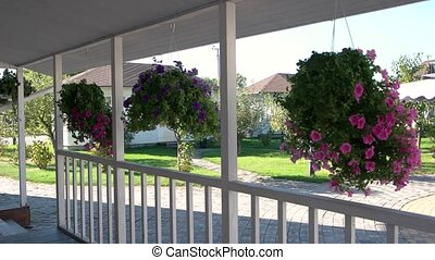 Flowers hanging on porch. Building and garden. Real estate...