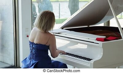 Woman playing white piano closeup