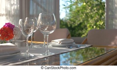 Dining table with flower vase. Empty shiny wineglasses.