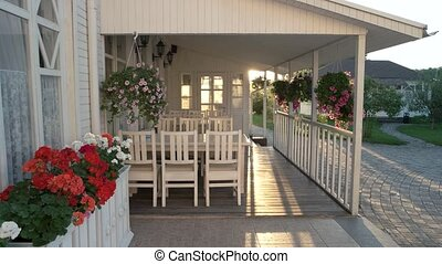 Flowers hanging on a porch. White colored house and...