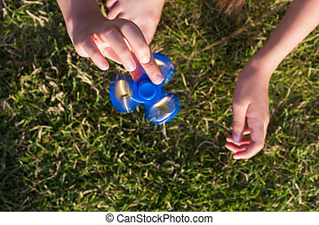 A teenager girl holds spinners. Modern toys. Fashion...