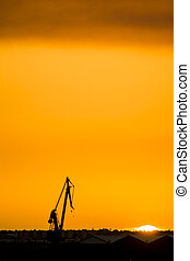 Landscape of a cranes in a harbor at sunset with clouds