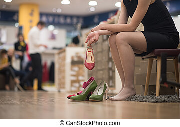 woman sitting in shoe store - Hard choice. Close-up of young...