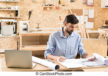 Concentrated youthful bearded man doing his job in work-room