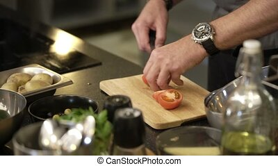 Cook cutting tomatoes with knife