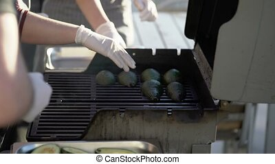 Cooking avocados at grill outdoors