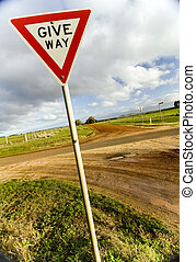 Give Way Sign - A give way / yield sign at a country dirt...