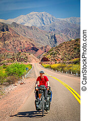 On the road to Cafayate - Woman cycling on the empty road to...