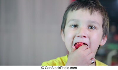 Little boy with brown hair eating a strawberry and showing...