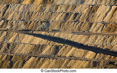Mining - Huge walls of moved earth with roads through it in...
