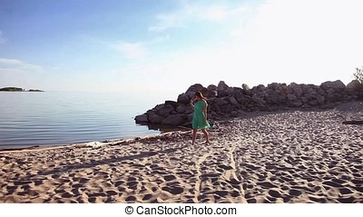 Overall plan. A beautiful girl in a green dress is walking along the coast.