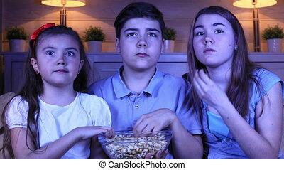 Children watching a horror film on TV