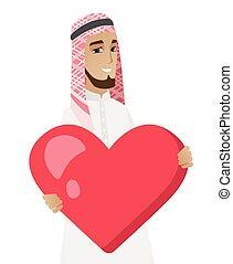 Muslim businessman holding a big red heart.