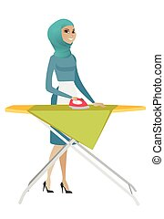 Muslim maid ironing clothes on ironing board. - Muslim maid...
