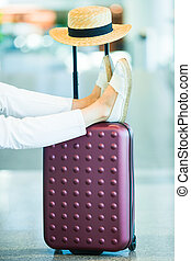 Close-up female legs, hat and baggage in airport indoor. Airline passenger in an airport waiting for flight aircraft