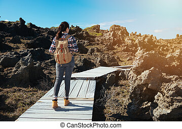 woman hiker looking view of beach with reef rocks landscape...