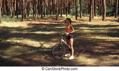 cutie young girl driving a bike in the wood