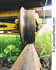 Cargo wagon wheel stay on rusty railway. Old railway wagon wait in depot. Fresh green gras