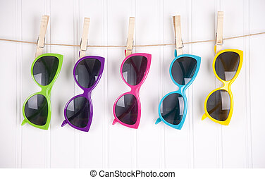 Vibrant Summer Sunglasses - Hip summer sunglasses hanging on...