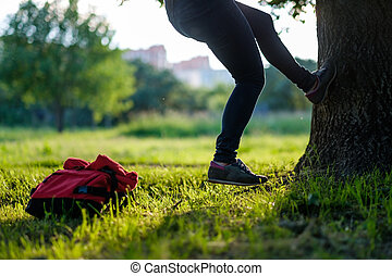 Young hipster man climbing on a tree in a park. Bag lying on...