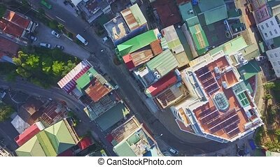 Drone Shows Street with Coloured Rooftops and Slow Traffic -...