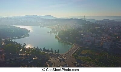 Drone Removes from Lake among Modern City in Morning - drone...