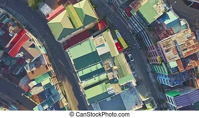 Drone Approaches Colourful Roof Terraces in Tropical City -...