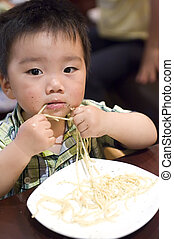 eating baby to grab pasta with hand