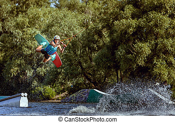 Sports training on a wakeboard. Jumping over water and...