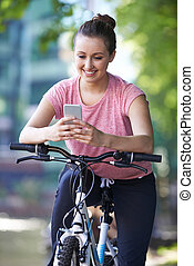Young Woman Using Mobile Phone Whilst Out On Cycle Ride