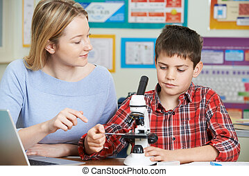 Teacher With Male Student Using Microscope In Science Class
