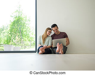 couple using laptop on the floor at home - Young couple...