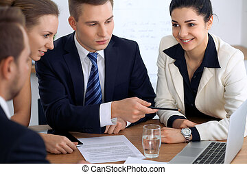 Business people or lawyers at  meeting in the office. Focus on a man pointing into laptop