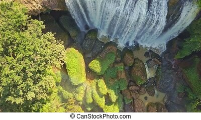 Flycam Moves from Green Boulders up to Giant Waterfall Top -...