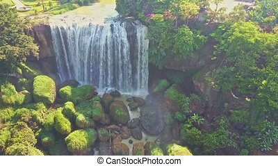 UAV Flies Close to Waterfall Bottom with Large Green...