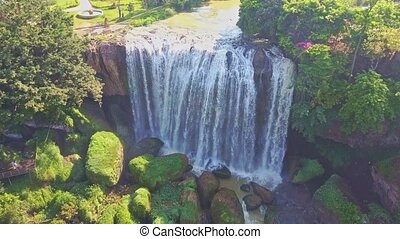 Flycam Opens View of Waterfall against Plants Boulders Sky -...