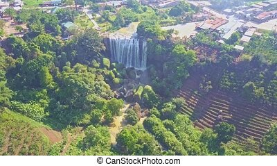 Aerial View Waterfall Runs among Tropical Plants by Village...