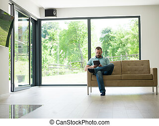 man on sofa using tablet computer