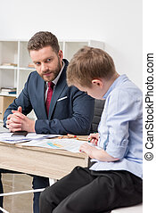 Businessman with his son drawing on business papers at office