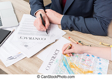 Businessman drawing on business papers with son at office