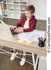 Young schoolboy using fathers laptop at office