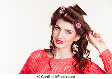 girl with curling irons makes hair style - A girl prepares...