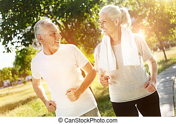 Cheerful retired smiling couple jogging together - Regular...