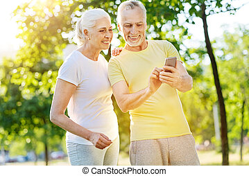 Positive aged couple resting in the park