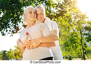 Low angle of positive loving aged couple in the park