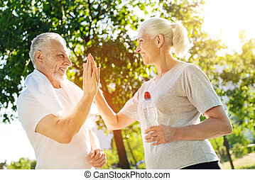 Positive aged couple resting in the park after jogging